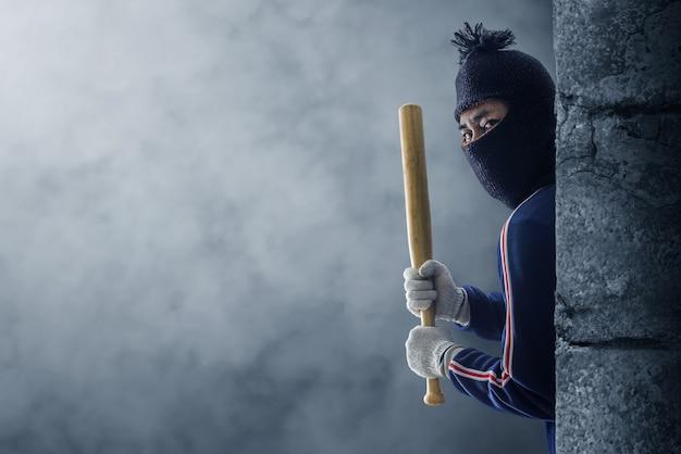 Criminoso ou bandido segurando um taco de beisebol. Foto Premium