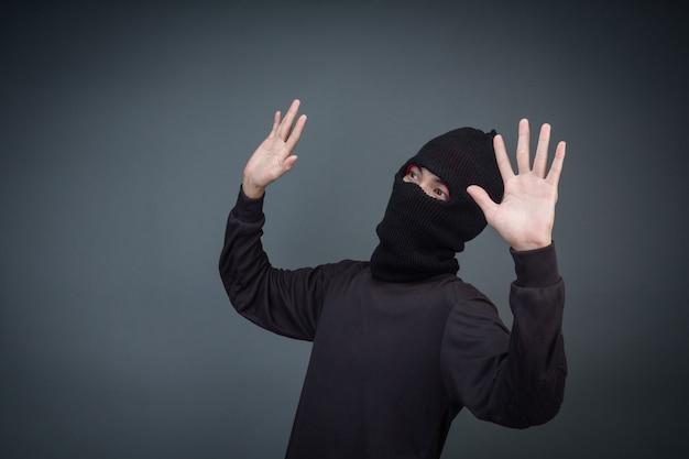 Criminosos usam uma máscara em preto sobre cinza Foto gratuita