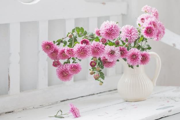Crisântemos rosa no jarro no velho banco de madeira branco Foto Premium
