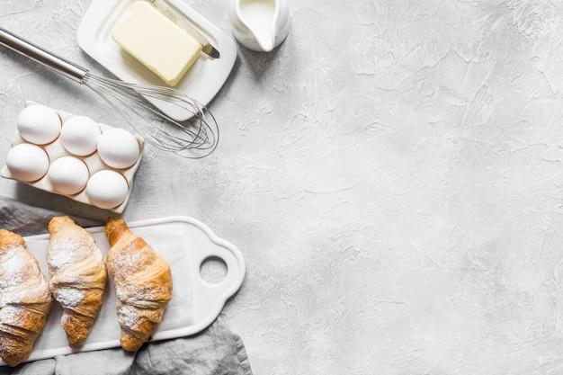 Croissant clássico da receita do conceito com os ingredientes para cozinhar a massa. acessórios de panificação e alimentos. Foto Premium