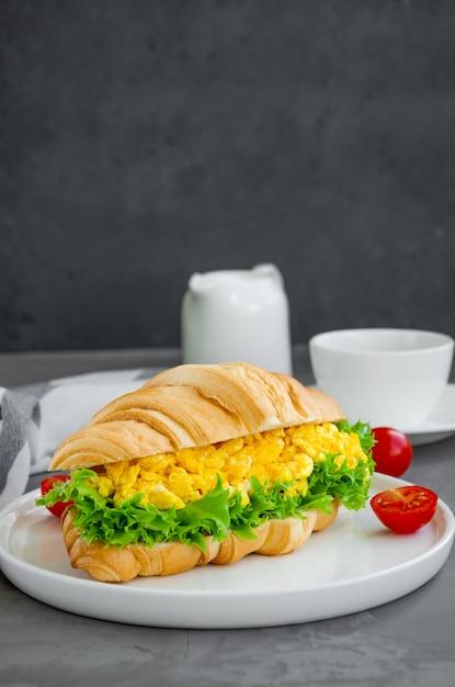 Croissant com ovos mexidos, alface e tomate cereja Foto Premium