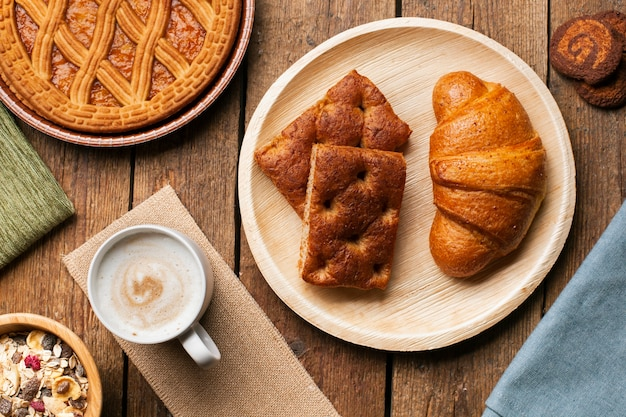 Croissant e bolo com cappuccino Foto gratuita