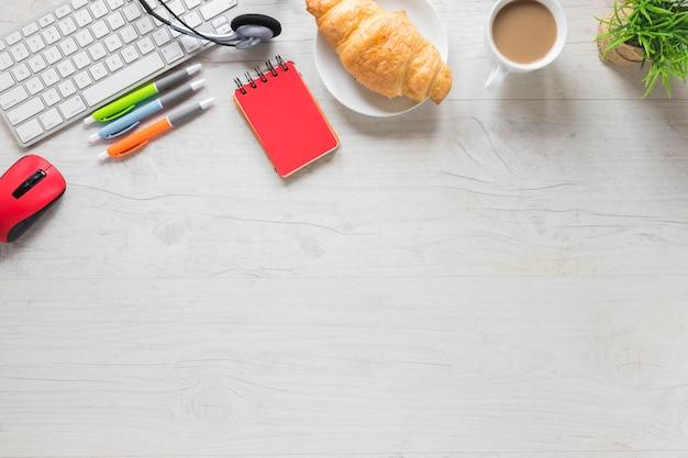 Croissant e xícara de chá com teclado e material de escritório na mesa de madeira com espaço para escrever texto Foto gratuita