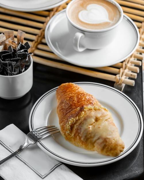 Croissant francês meio mergulhado em creme de baunilha Foto gratuita