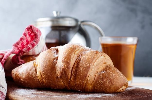 Croissant fresco com chá no café da manhã. fundo de fotografia de comida. Foto Premium