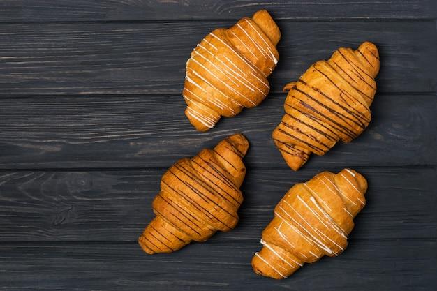 Croissant fresco em um fundo preto de madeira. vista superior copie o espaço Foto Premium
