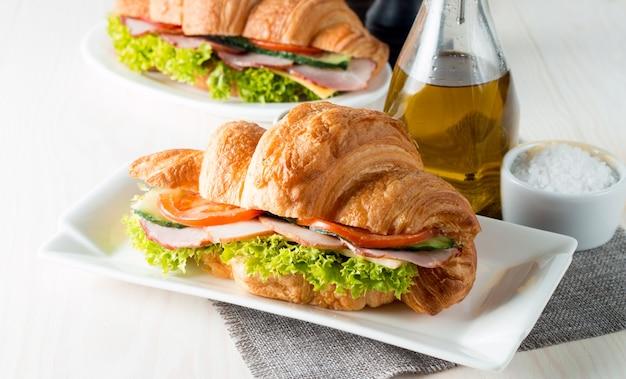 Croissant ou sanduíche fresco com salada, presunto no fundo de madeira. Foto Premium