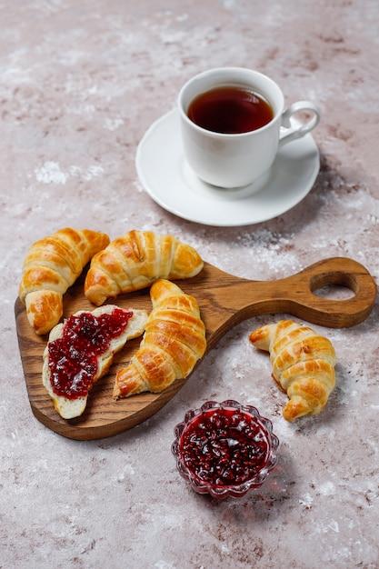 Croissants caseiros saborosos frescos com geléia de framboesa em cinza-branco. pastelaria francesa Foto gratuita