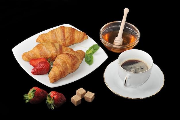 Croissants com café e mel na superfície preta Foto Premium