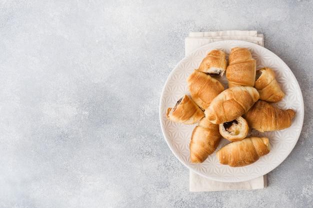 Croissants com recheio de chocolate em uma superfície de placa cinza Foto Premium