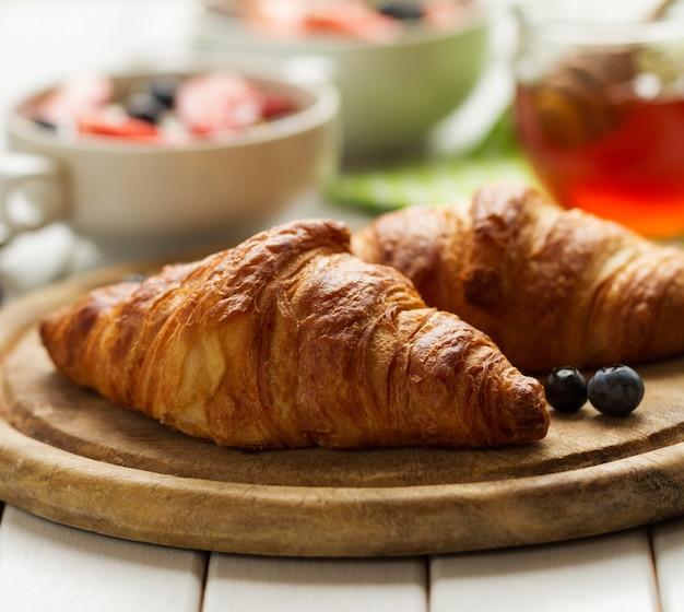 Croissants deliciosos e saborosos na placa de madeira. Pequeno-almoço continental tradicional. Granola com frutas e mel no fundo. Foto gratuita