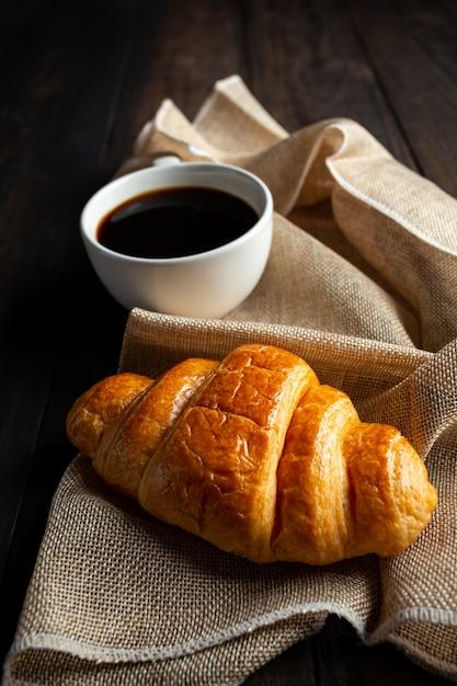 Croissants e café na mesa de madeira velha. Foto gratuita