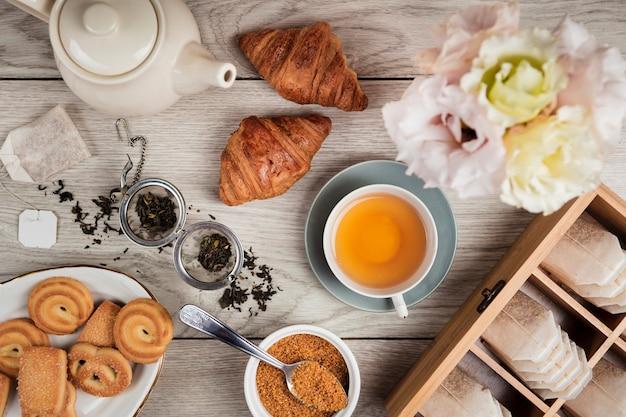 Croissants e chá em fundo de madeira Foto gratuita