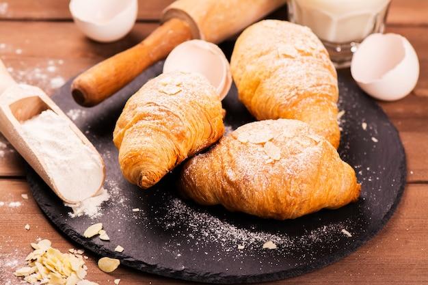 Croissants frescos assados com folhas de amêndoa Foto Premium