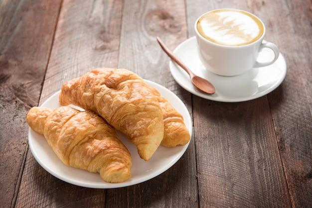 Croissants frescos e café na mesa de madeira Foto Premium