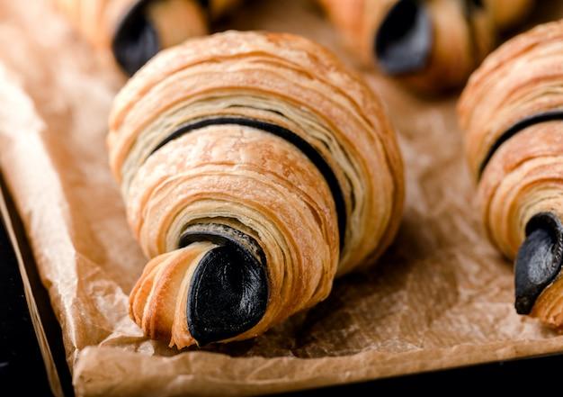 Croissants recém-assados com chocolate na bandeja de metal preto em pergaminho Foto Premium