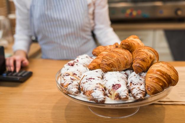 Croissants recém-assados no carrinho do bolo no balcão da loja de café Foto gratuita