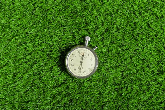 Cronômetro prateado na grama verde Foto Premium