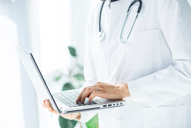 Crop doctor browsing laptop no escritório Foto gratuita