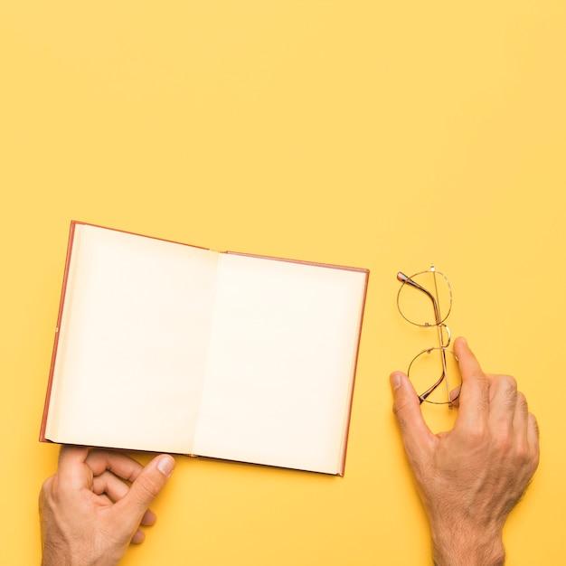 Crop masculino segurando óculos e abrir o caderno Foto gratuita