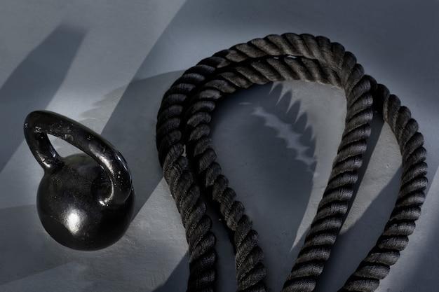 Crossfit kettlebell e corda de batalha no ginásio Foto Premium