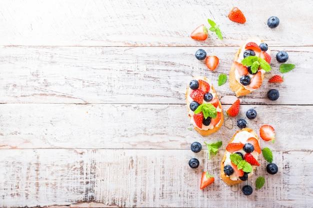 Crostini com baguete grelhado, cream cheese e frutas vermelhas Foto Premium