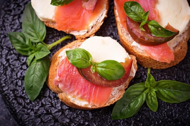 Crostini com salmão, mozarella, tomate e manjericão Foto Premium