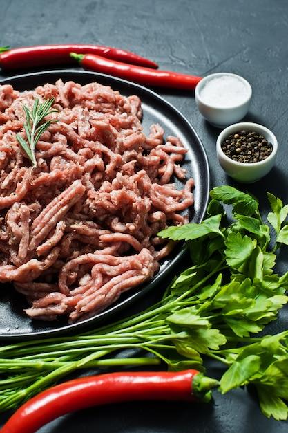 Cru triturado em uma placa preta. ingredientes para cozinhar, alecrim, pimenta, alho, sal, salsa, endro. Foto Premium