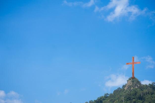 Cruz de madeira sobre a montanha e o fundo do céu azul Foto Premium