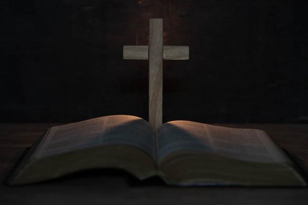Cruz e bíblia sagrada na mesa de madeira Foto gratuita