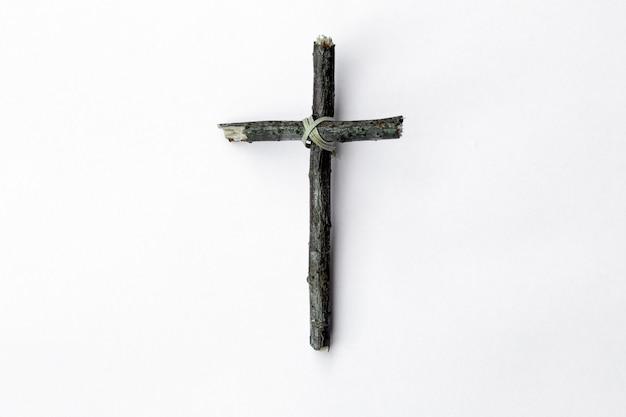 Cruz feita de galho de árvore isolado no fundo branco Foto Premium