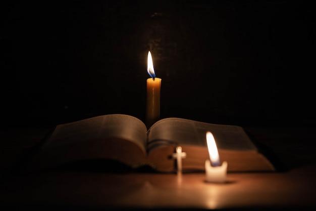Cruze com a bíblia e vela em uma velha mesa de madeira de carvalho. Foto gratuita