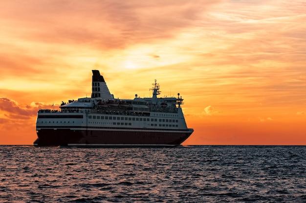 Cruzeiro em mar aberto. balsa de passageiros navegando ao pôr do sol quente Foto Premium