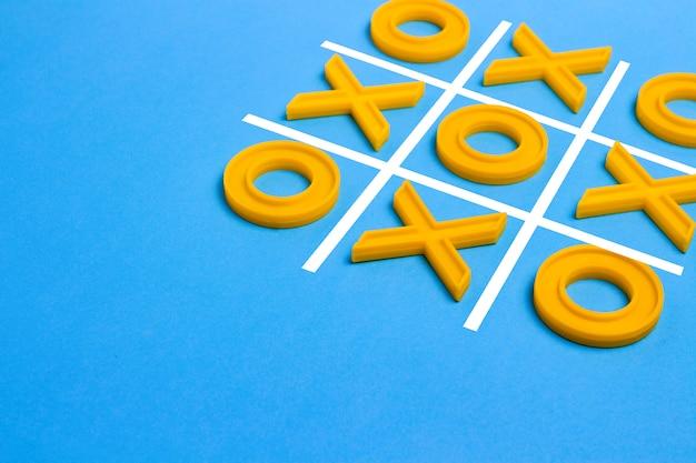 Cruzes de plástico amarelas e um dedo do pé e um campo regulamentado para jogar jogo da velha sobre um fundo azul. conceito xo vence o desafio. jogo educativo para crianças Foto Premium