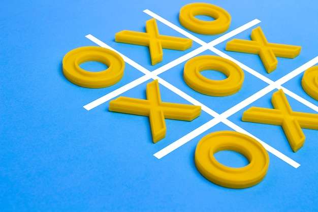 Cruzes de plástico amarelo e um dedo do pé e um campo regulamentado para jogar tic-tac-dedo do pé em uma superfície azul. conceito xo vence o desafio. jogo educativo para crianças Foto Premium