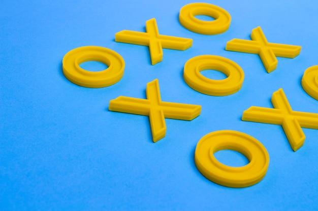 Cruzes de plástico amarelo e zeroches para jogar jogo da velha em uma superfície azul. conceito xo vence o desafio. jogo educativo para crianças Foto Premium