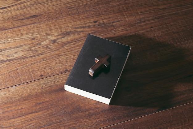 Cruzes e livros sobre uma mesa de madeira Foto Premium