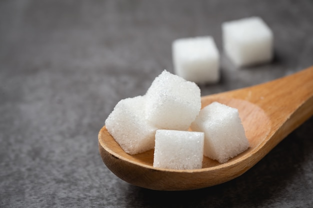 Cubo de açúcar branco na colher de pau na mesa. Foto gratuita