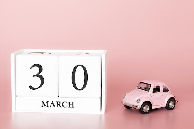 Cubo de madeira 30 de março. dia 30 do mês de março, calendário em um fundo rosa com carro retrô. Foto Premium