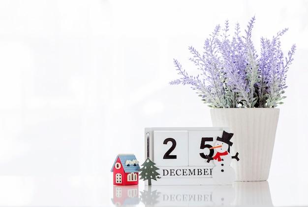 Cubo de madeira calendário mostrando data em 25 de dezembro com casa de madeira, planta de casa e boneco de neve Foto Premium