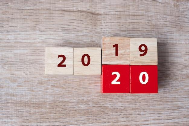 Cubo de madeira com flip sobre o bloco 2019-2020 palavra no fundo da tabela Foto Premium