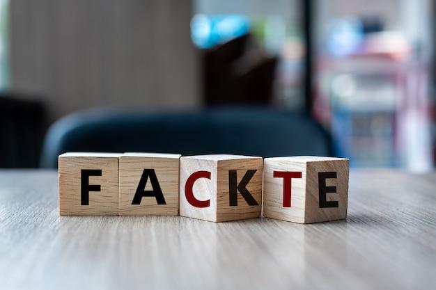 Cubo de madeira com virar o bloco fake to fact word Foto Premium