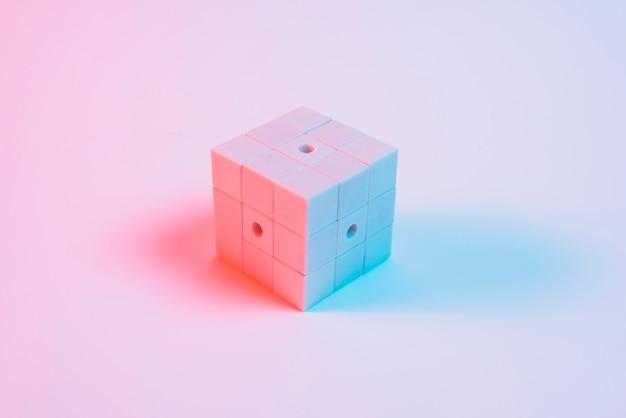 Cubo de quebra-cabeça pintado com luz azul e sombra contra o pano de fundo-de-rosa Foto gratuita