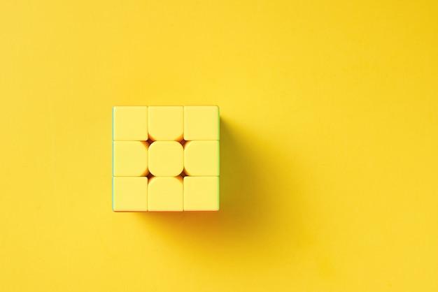 Cubo de rubics em um fundo amarelo, vista superior Foto Premium