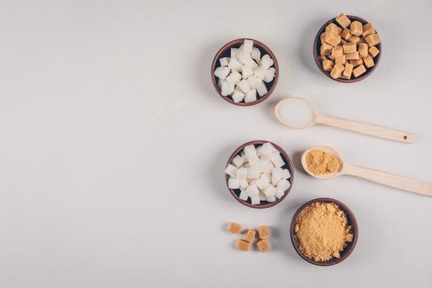 Cubos de açúcar branco e marrom em taças com vista superior de colheres Foto gratuita
