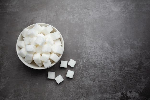 Cubos de açúcar branco em uma tigela na mesa. Foto gratuita