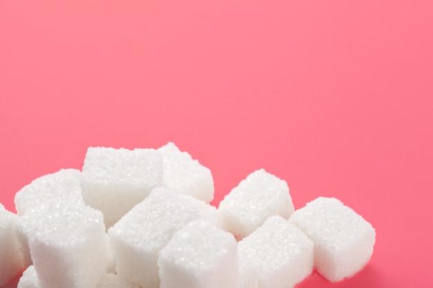 Cubos de açúcar em um fundo rosa. Foto Premium