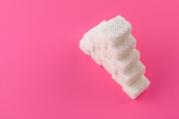 Cubos de açúcar em um rosa. texto de cópia de espaço vazio Foto Premium