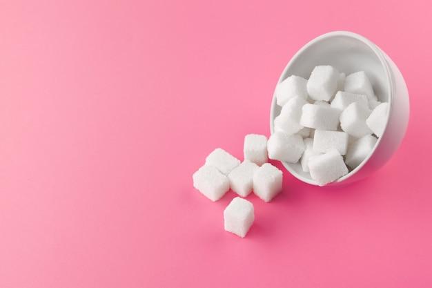 Cubos de açúcar em uma tigela sobre fundo rosa Foto Premium