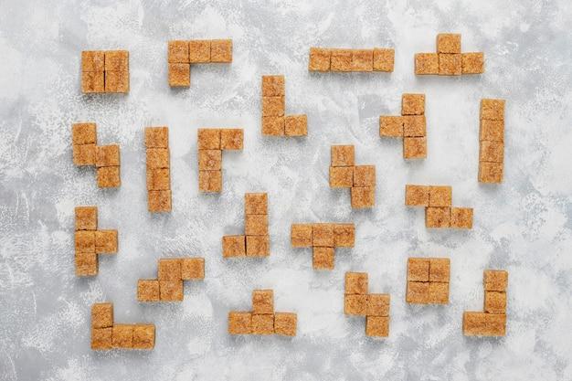 Cubos de açúcar mascavo no concreto, vista superior Foto gratuita